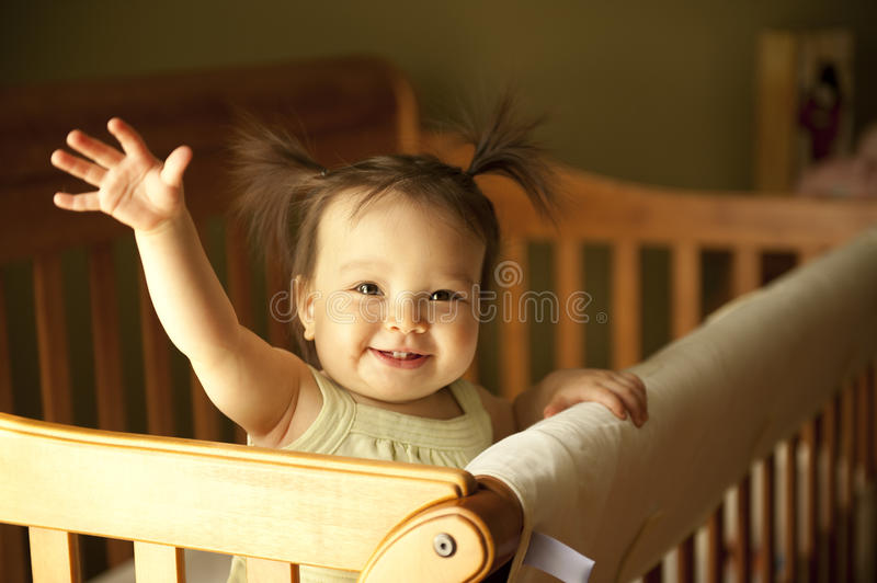 Baby standing up in crib. Baby girl waving hand and standing up in crib stock image