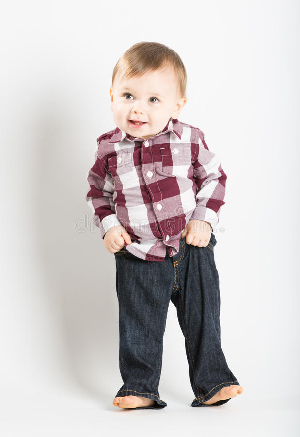 Free Baby Stands In Flannel And Jeans Pulling Up Pants Royalty Free Stock Photo - 61713665