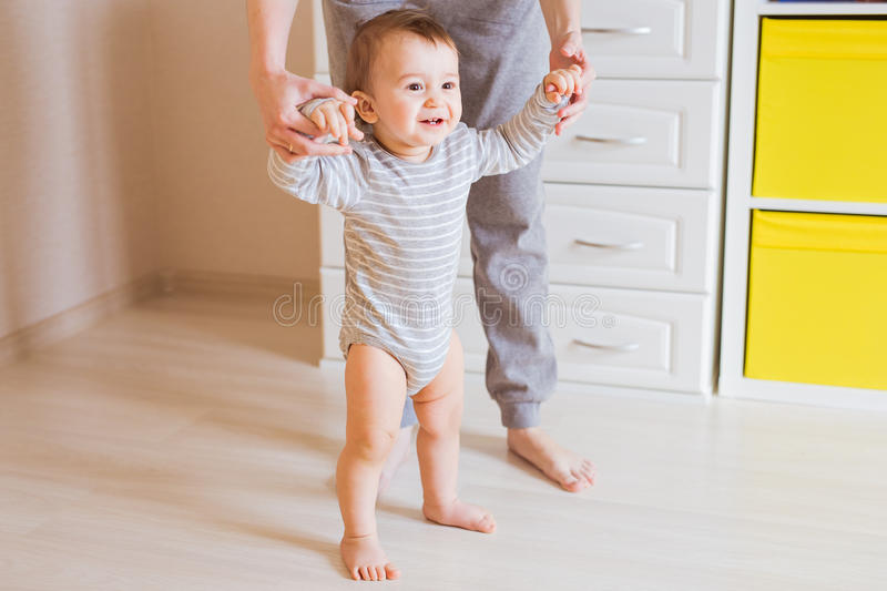 Baby steps with the help of his mother royalty free stock image