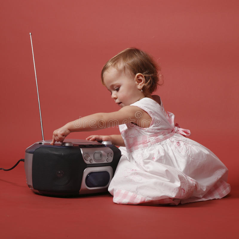 Baby with stereo radio. Color photo of baby girl switching on stereo radio, studio shot , red background royalty free stock image