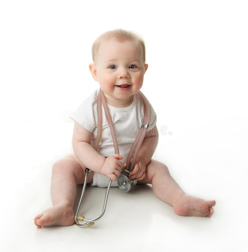 Baby with stethoscope. Adorable baby sitting up wearing and playing with a medical stethoscope, isolated on white royalty free stock image