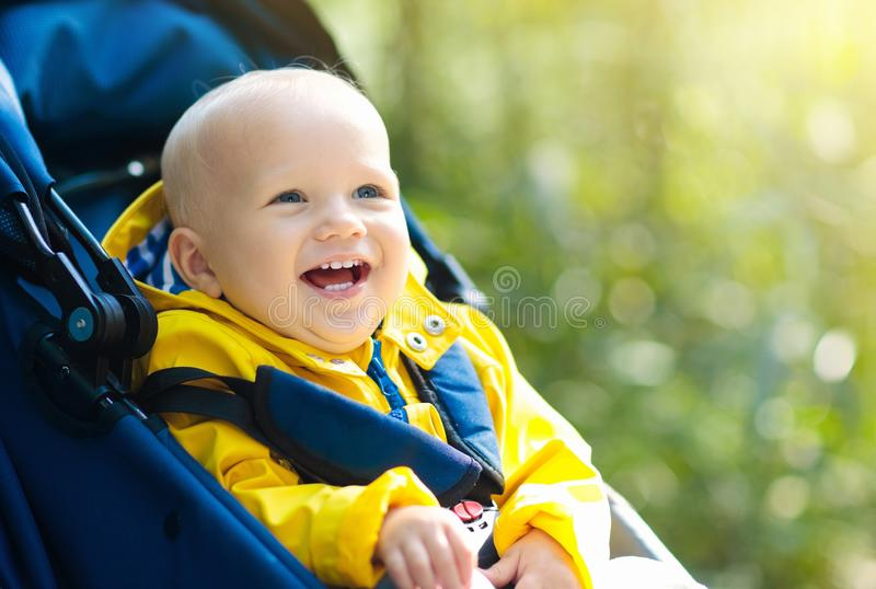 Baby boy in stroller in autumn park. Baby in stroller on a walk in autumn park. Adorable little boy in green jacket sitting in colorful pushchair under warm stock photos