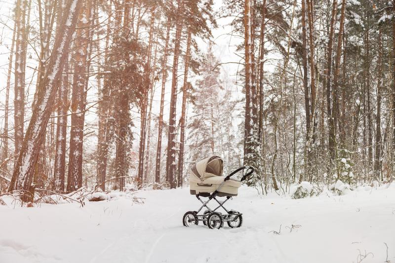 Baby stroller in winter forest. Infant baby sleep inside the pram on fresh air.  royalty free stock images