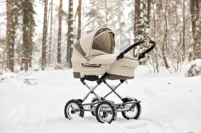 Baby stroller in winter forest. tire tracks on snow. Infant baby sleep inside the pram on fresh air.  royalty free stock image