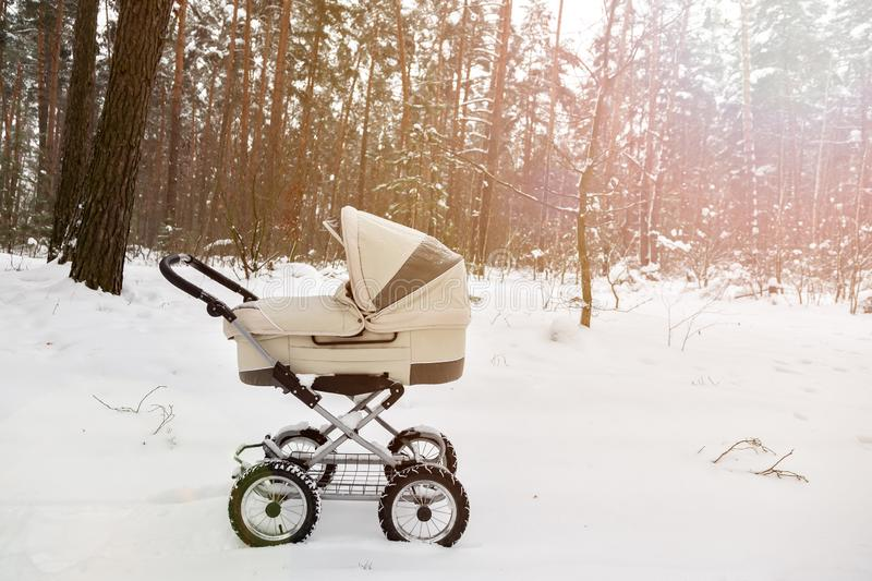 Baby stroller in winter forest. tire tracks on snow. Infant baby sleep inside the pram on fresh air.  royalty free stock photography