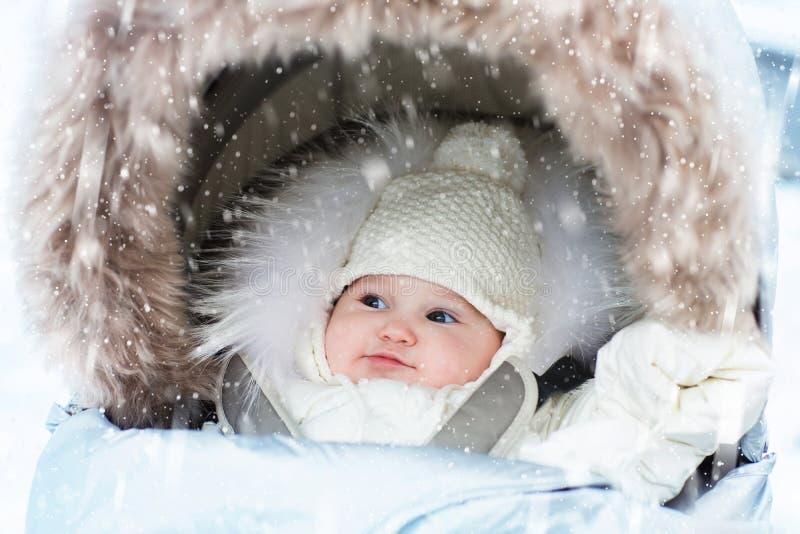 Baby in stroller in winter snow. Kid in pram royalty free stock photo