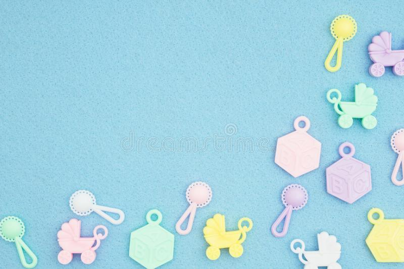 Baby strollers, abc blocks and rattles on an blue textured material background stock image