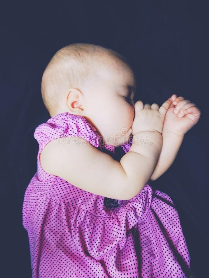 The baby sucks a thumb in a sleep stock image