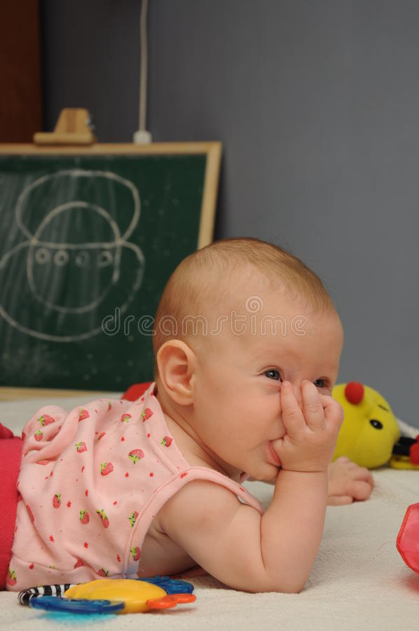 Baby sucks thumb. Beautiful baby sucking her thumb and thinking about life stock image