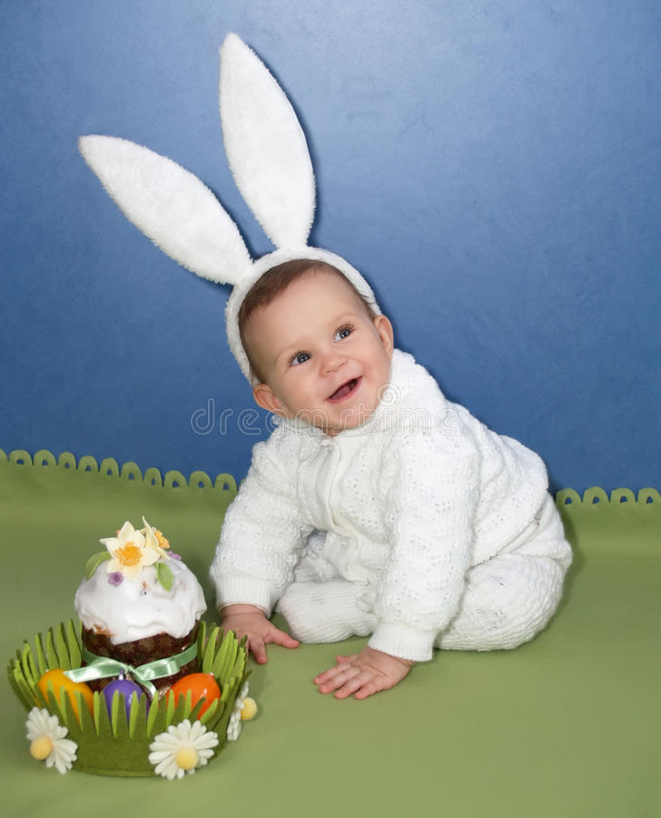 The baby in a suit of the hare with an easter Easter cake stock photos