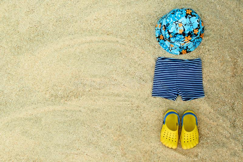 Baby summer beachwear, flip flops, hat, shorts on sand beach stock images