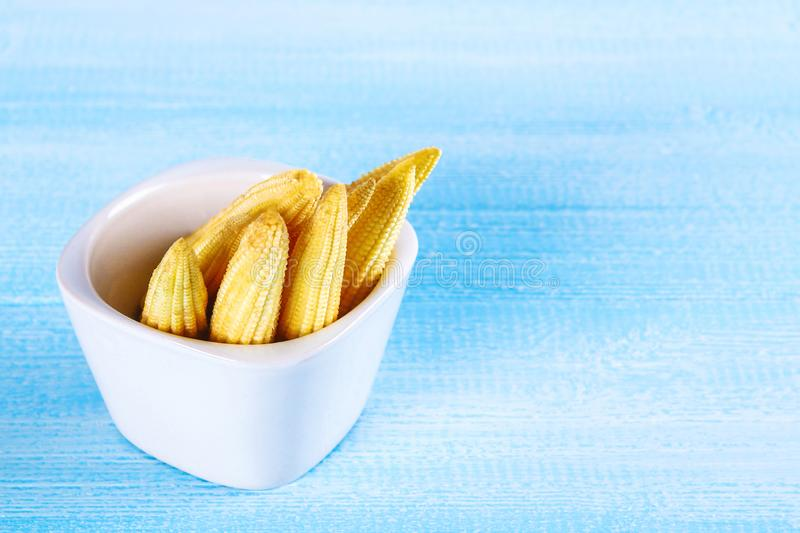 Baby sweetcorn or mini corn. It is typically the eaten whole cob included for the human consumption. It is eaten both raw and cook. Ed. Baby corn is common in stock photography