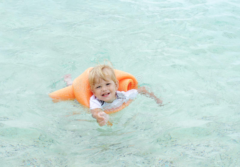 Baby swimming in Ocean. Baby swimming in clear blue ocean water with support of a noodle stock photos