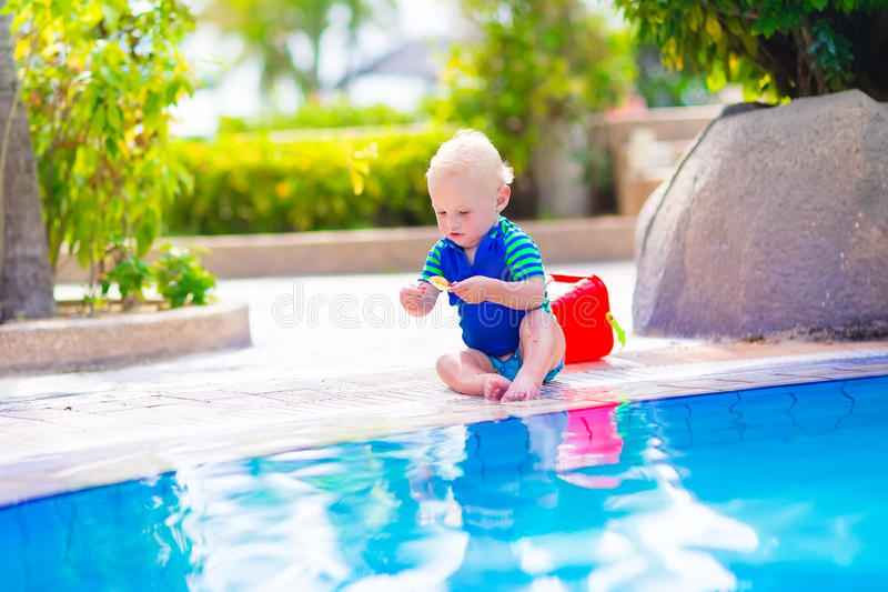 Baby at swimming pool. Cute funny baby boy playing with red toy bucket sitting at a swimming pool in a tropical resort on a hot summer day stock photo