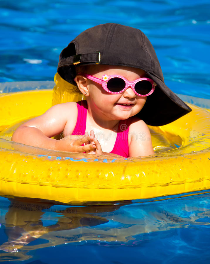 Baby swimming in a pool. With float stock photos