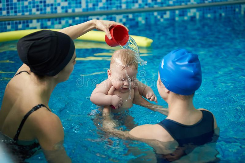 Baby in swimming pool and two women. Little boy afraid and holding his eyes closed while woman pouring water on his head stock image