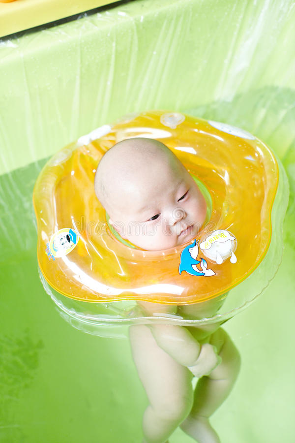 Baby swimming. Two month old baby is swimming royalty free stock photo