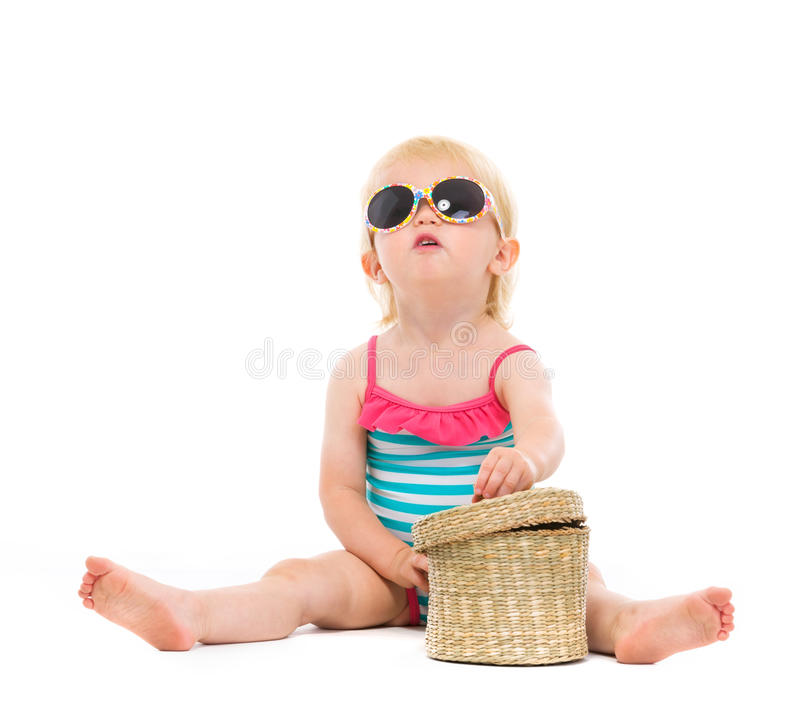 Baby in swimsuit and sunglasses looking up. Isolated on white stock images