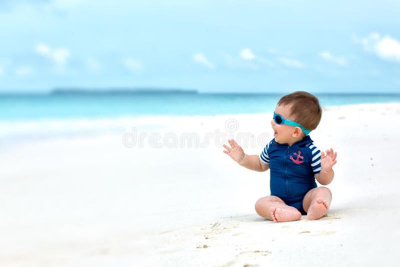 Baby in swimwear having vacation. Cute baby smiling, sitting on white sandy tropical beach on Maldives, having vacation. With diving costume or swimwear royalty free stock image