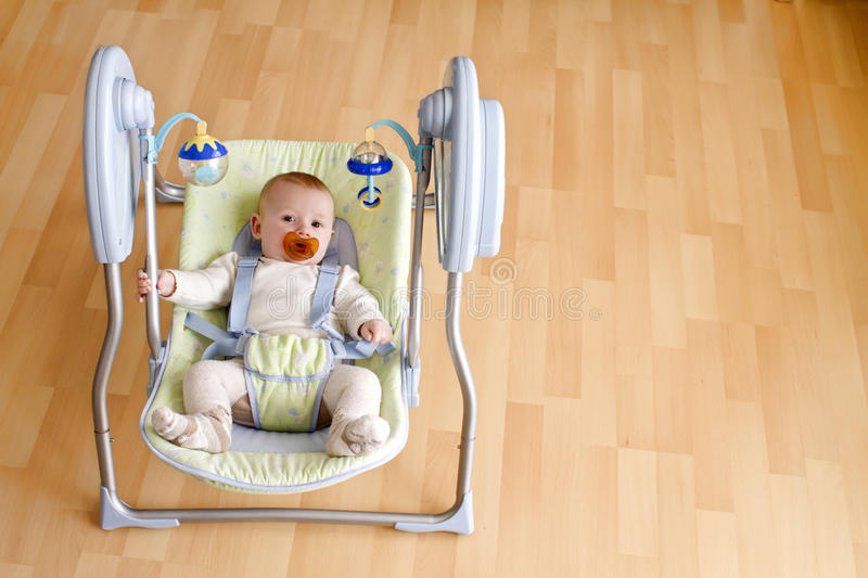 Baby in swing. Baby swinging at home in an electronic swing, with copy space stock photos