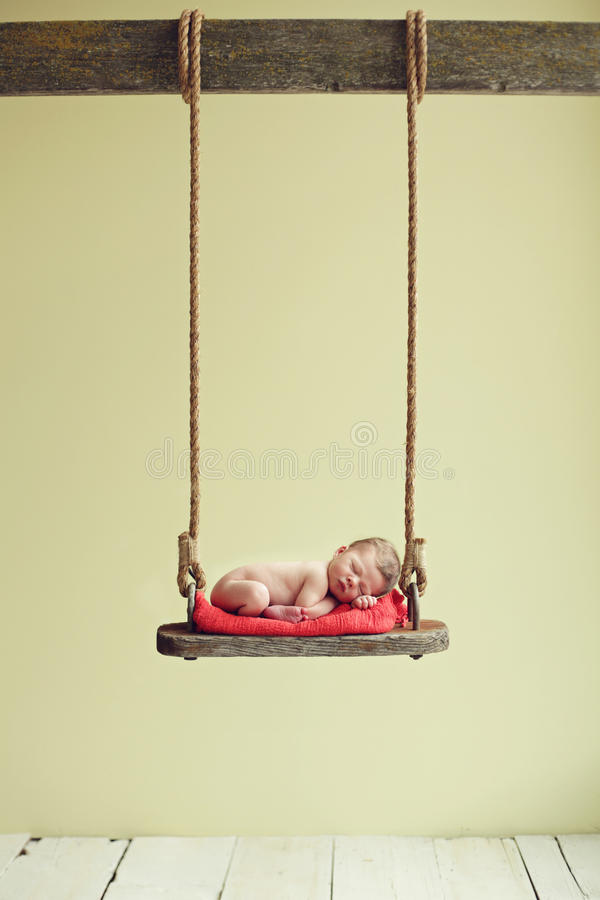 Baby on a swing. Newborn baby boy sleeping on an antique swing royalty free stock photography
