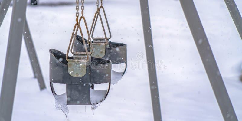 Baby swings against snow covered ground in Utah stock images