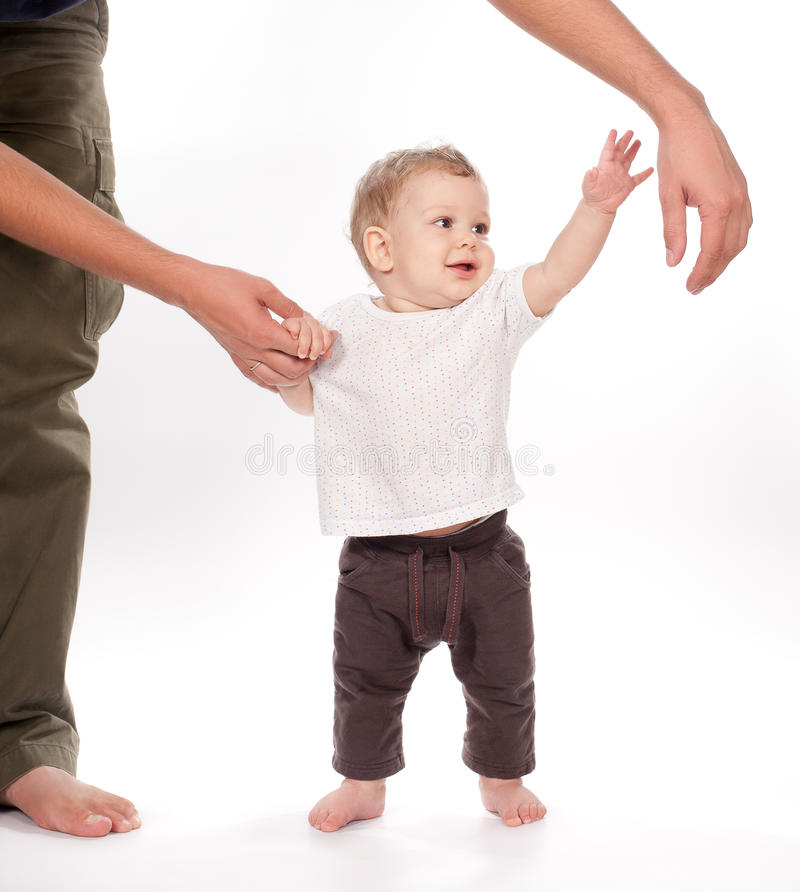 Baby taking first steps with father help on white