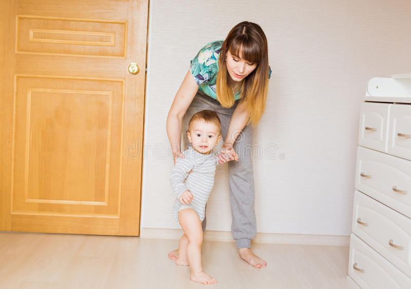 Baby taking first steps with mother help stock images
