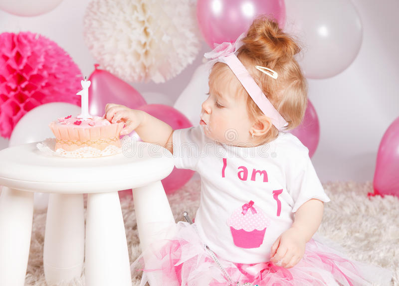 Baby tasting her birthday cake. Hungry baby eating the birthday cake with hand royalty free stock images