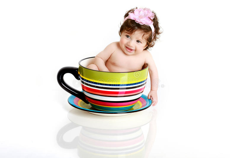 Baby in tea cup. Three months old cute little baby girl sitting in a teacup
