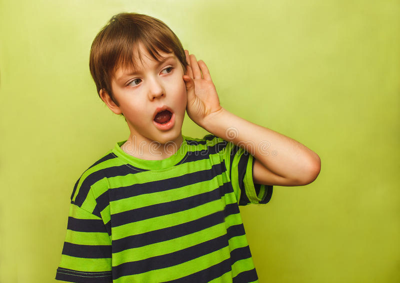 Baby teenager boy listens to put a hand his ear on. Baby teenager boy listens to put a hand to his ear on a green background royalty free stock images