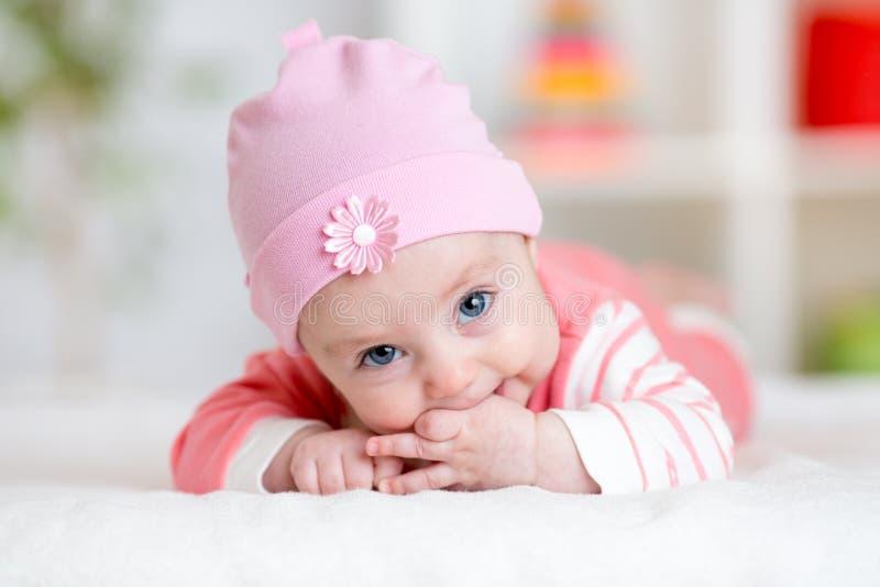 Baby teething sucks fingers. Infant kid lying in nursery. Room stock photo