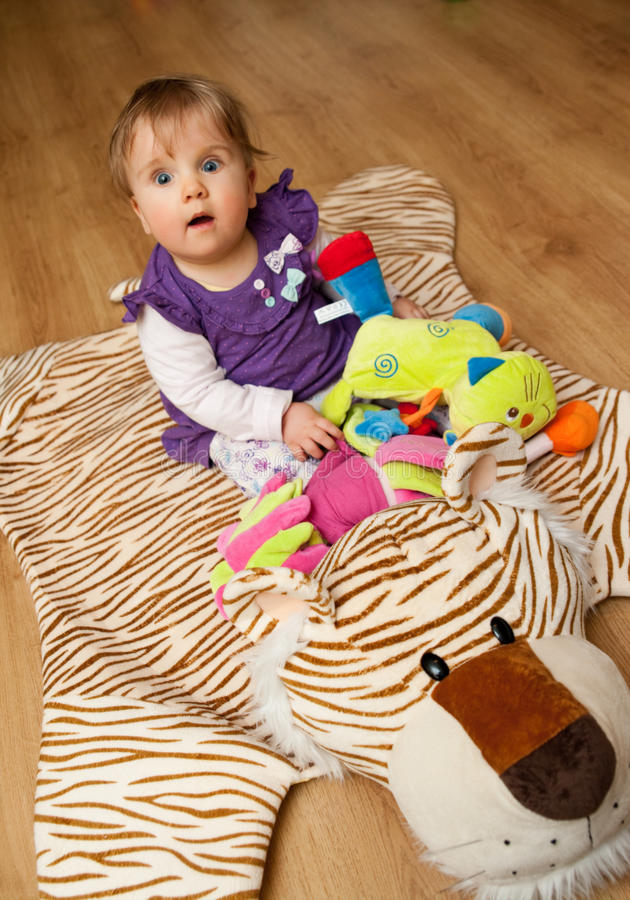 Baby on tiger mat. Cute baby girl sits on a tiger mat at home royalty free stock image