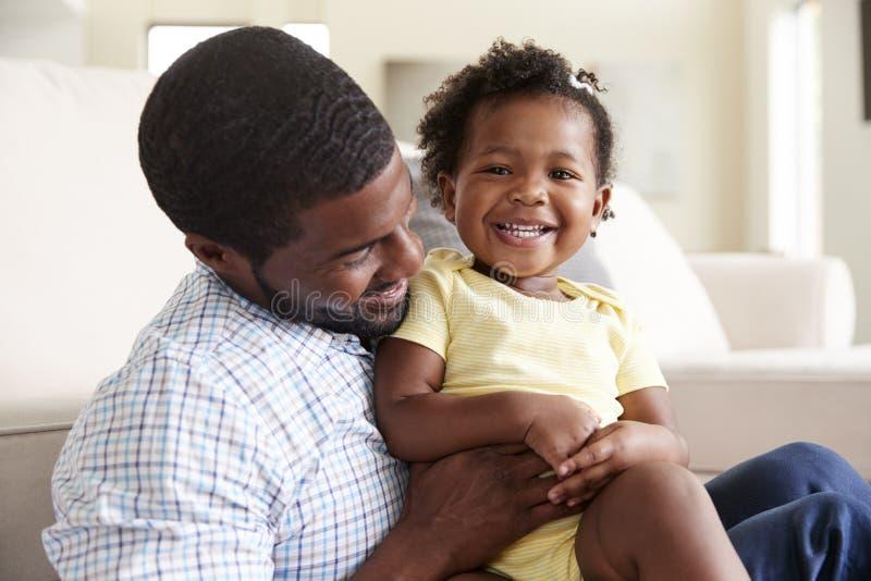Baby-Tochter, die mit Vater On Sofa In Lounge At Home spielt stockfoto