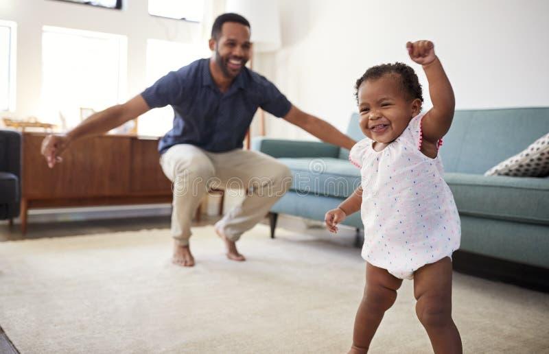 Baby-Tochter-Tanzen mit Vater-In Lounge At-Haus lizenzfreie stockfotografie
