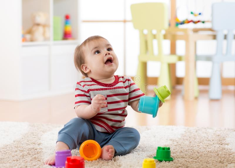 Baby toddler boy playing indoors with developmental toy sitting on soft carpet stock image