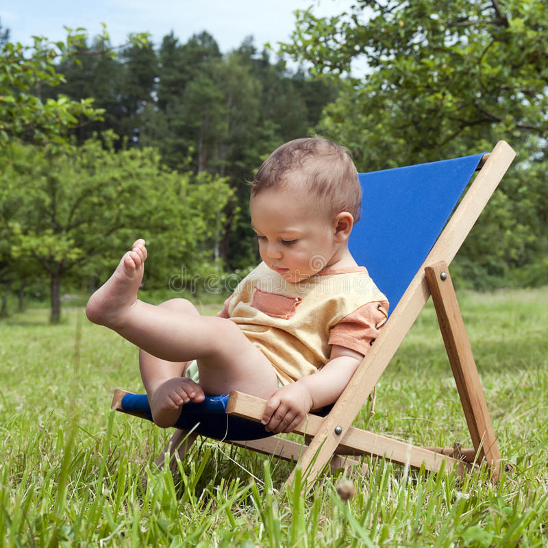 Baby on deckchair in garden royalty free stock image