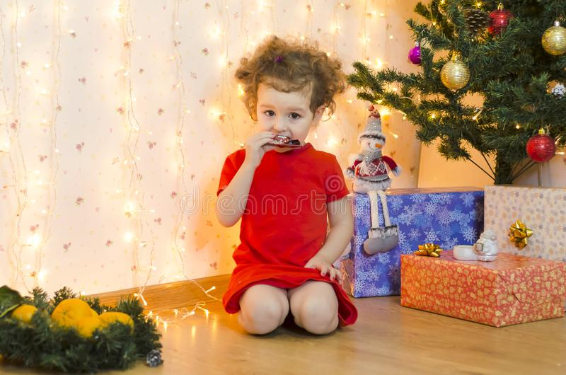 Baby toddler eats holiday treats, sweets, chocolate, tangerines royalty free stock images
