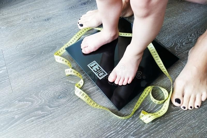 Baby or toddler feet on digital weight scale, mother monitor child's diet concept stock image
