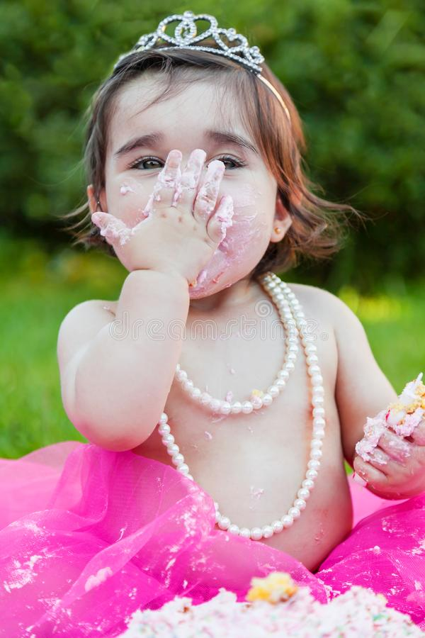 Baby toddler girl in first birthday anniversary party. Smiling happy baby toddler girl first birthday anniversary party. Licking hand with face dirty from pink royalty free stock image
