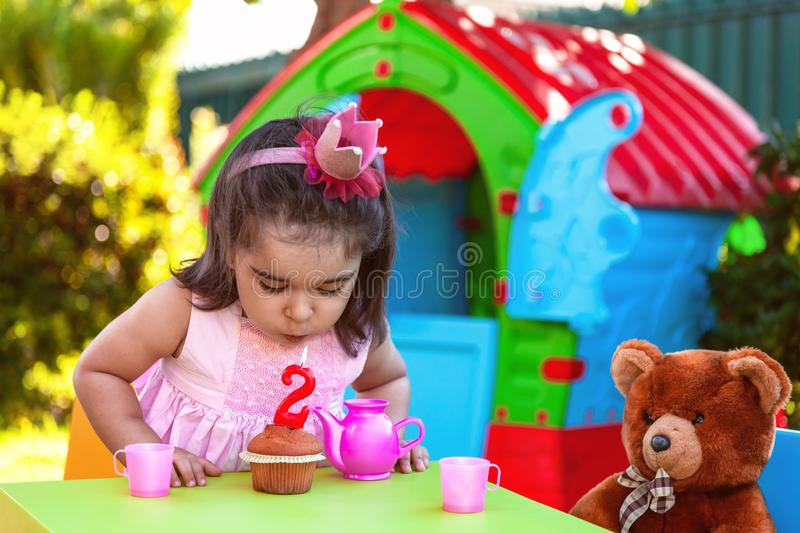 Baby toddler girl in outdoor second birthday party blowing candle on muffin. Teddy Bear as best friend, playhouse and tea set. Pink dress and crown royalty free stock photography