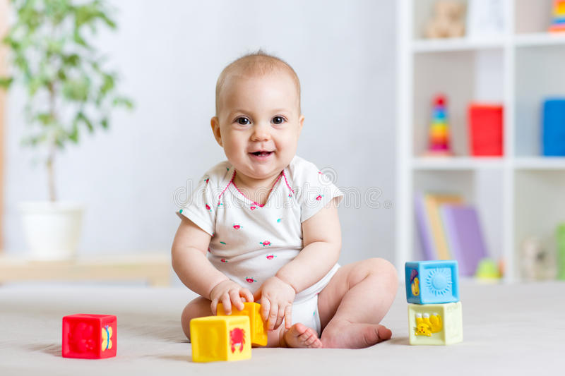 Baby toddler girl playing color toys at home or nursery royalty free stock photography