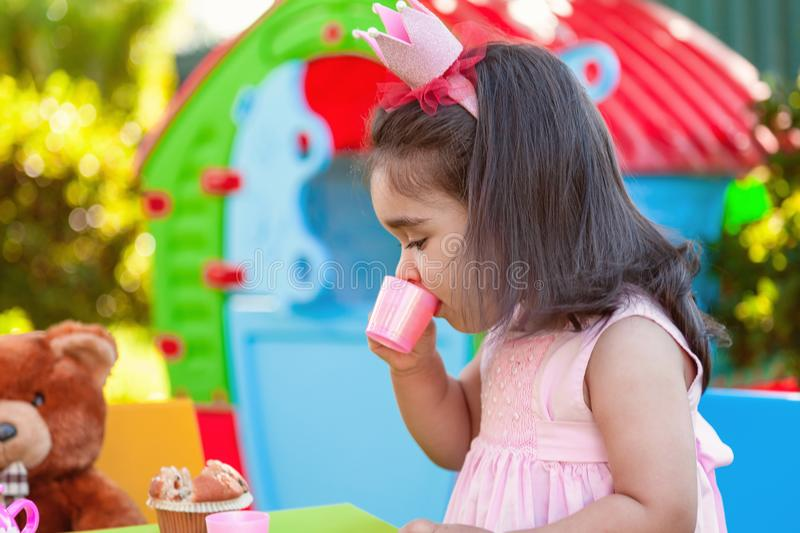 Baby toddler girl playing in outdoor tea party drinking from cup with best friend Teddy Bear stock photos