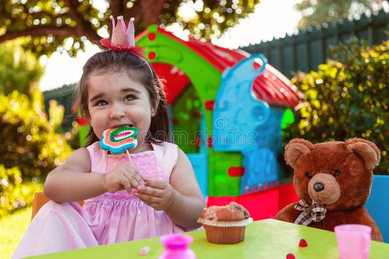 Baby toddler girl playing in outdoor tea party eating and biting a large lollipop with best friend Teddy Bear. Pink dress and queen or princess crown royalty free stock images