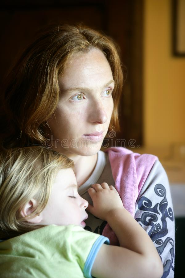 Baby toddler girl sleeping in mother arms. Baby toddler girl sleeping in redhead mother arms tranquil scene royalty free stock images