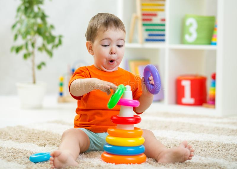 Baby toddler makes funny faces playing with toy on floor royalty free stock photography