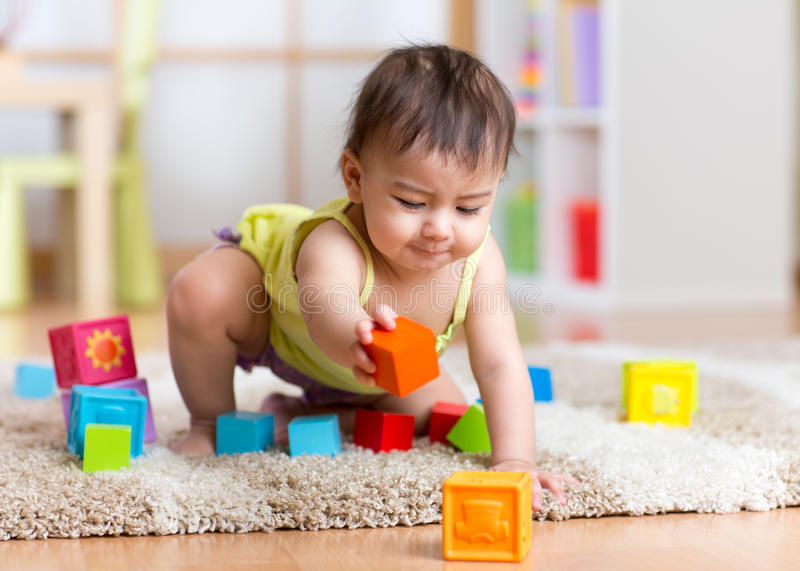 Baby toddler playing wooden toys at home or nursery. Kid toddler playing wooden toys at home or nursery stock photo