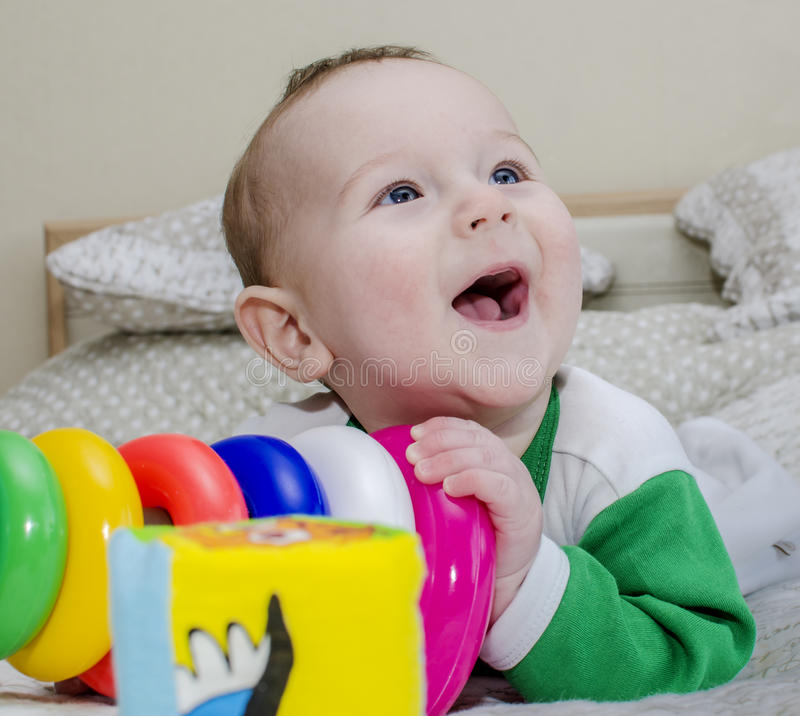 Download Baby Toddlers Surrounded By Toys Lying On The Bed. Stock Photo - Image: 83713622