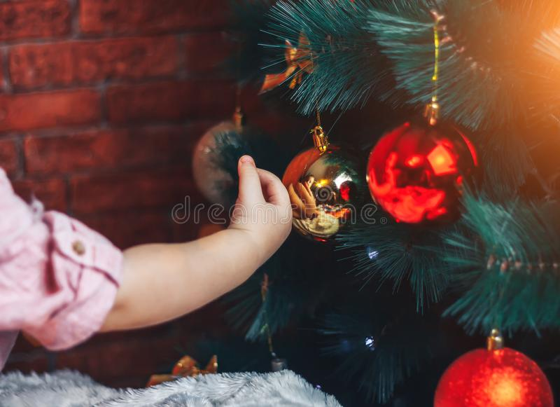 Baby touching chistmas toys on christmas tree, he try to put ball on the tree. Little baby boy is sitting on floor under Christmas tree and reaching for toy on stock photo