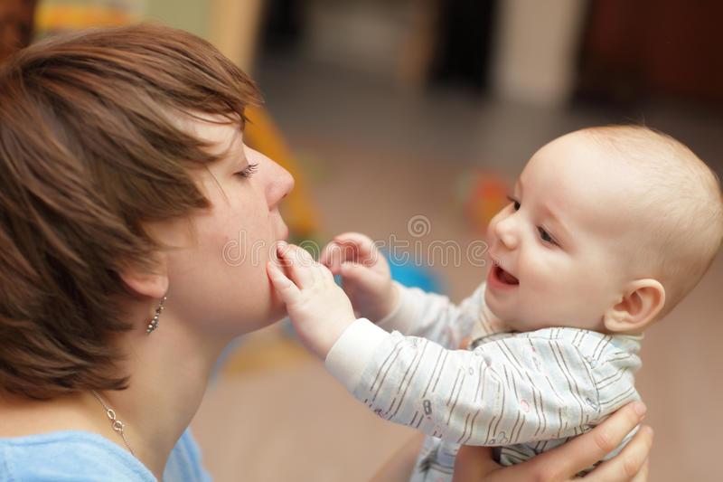 Baby touching his mother stock photos